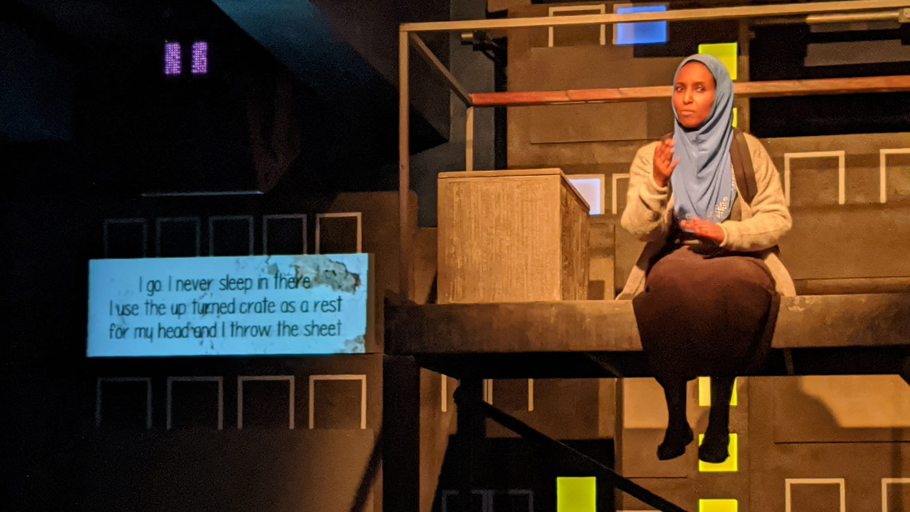 A girl sitting on a stage with captions to her left designed to look like a bus stop
