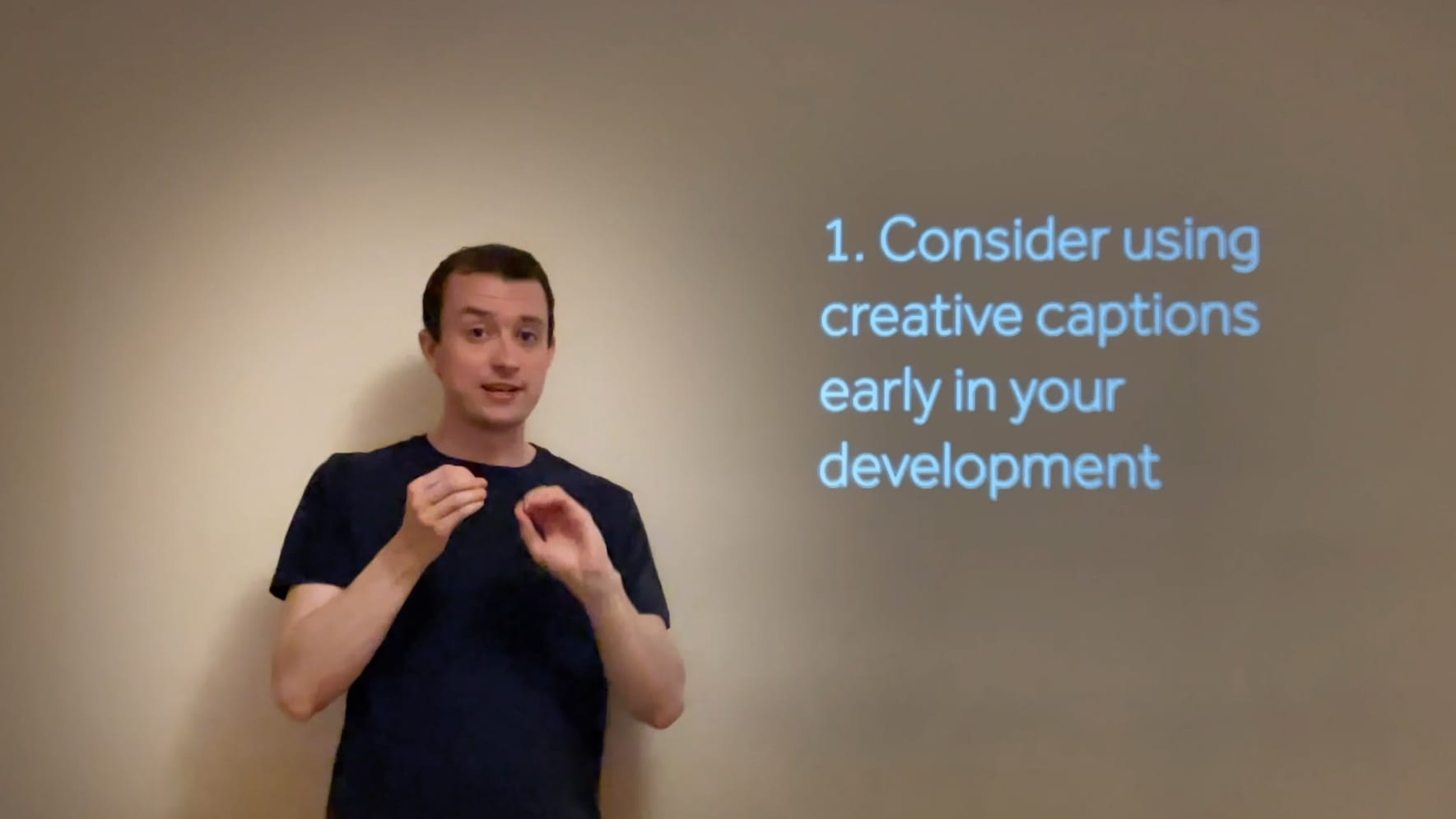 A man signing in front of captions saying 1. Consider using creative captions early in your development
