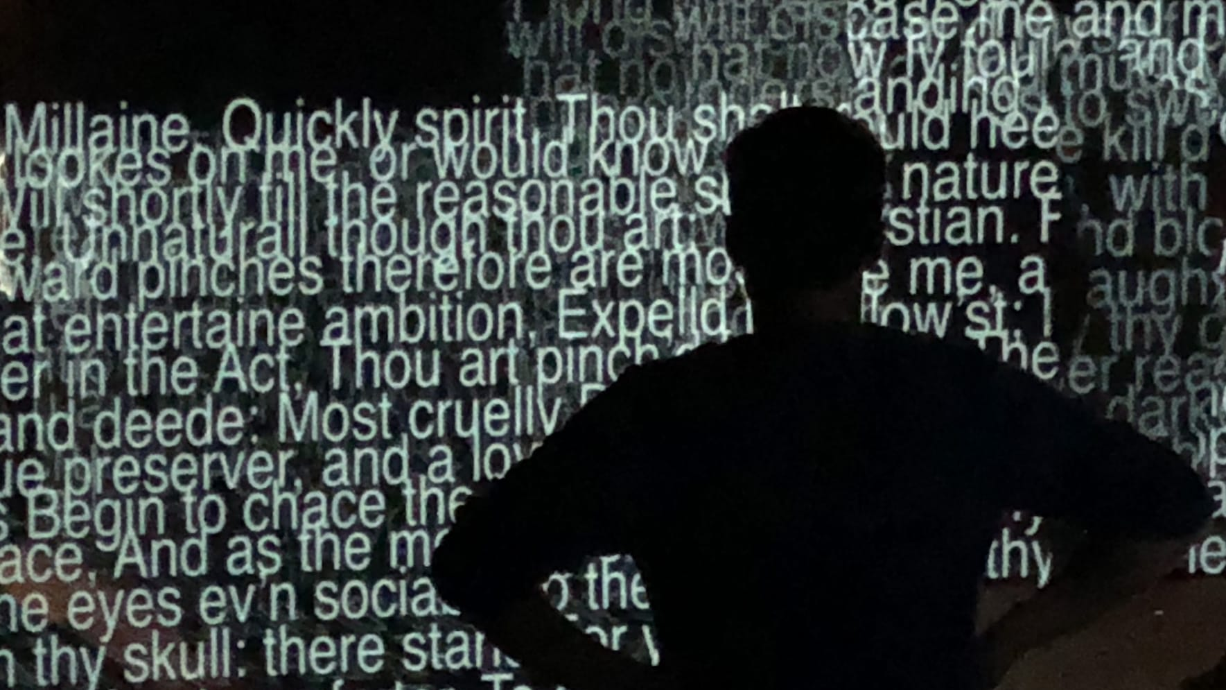 A silhouette of a man standing in front of a wall of projected captions